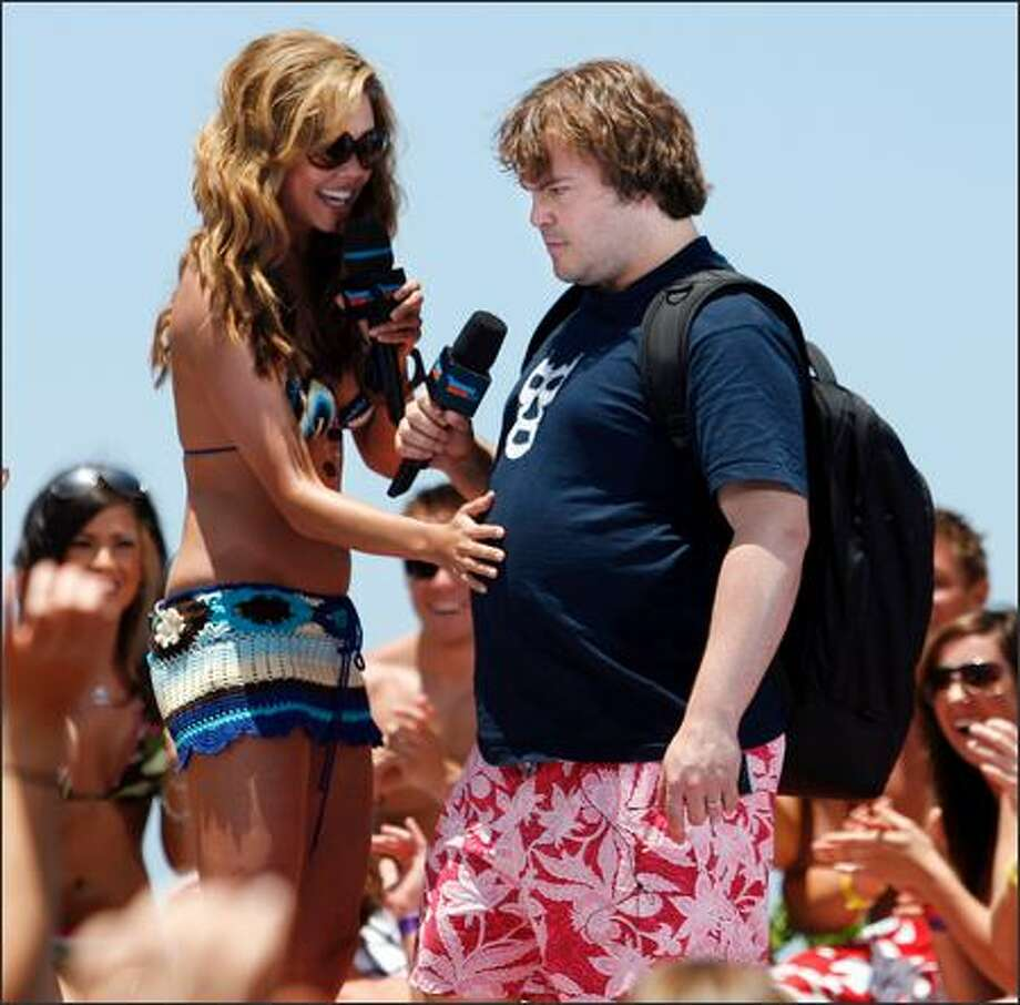 "MTV VJ Vanessa Minnillo checks out Jack Black's baby bump -- his signature, um, voluptuousness -- at a taping for MTV's ""Summer Sizzle '06"" at San Diego's Mission Beach. Photo: Associated Press / Associated Press"