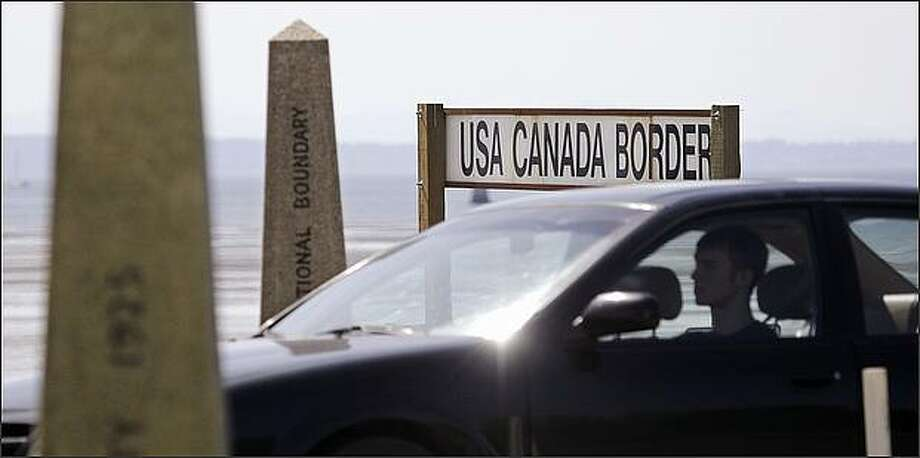 A driver headed toward the U.S. passes border markers Saturday at the border crossing between the U.S. and Canada in Blaine, Wash. New rules requiring passports or new high-tech documents to cross the United States' northern and southern borders are taking effect Monday, as some rue the tightening of security and others hail it as long overdue. In 2001, a driver's license and an oral declaration of citizenship were enough to cross the Canadian and Mexican borders; Monday's changes are the last step in a gradual ratcheting up of the rules. (AP Photo/Elaine Thompson) Photo: Associated Press / Associated Press