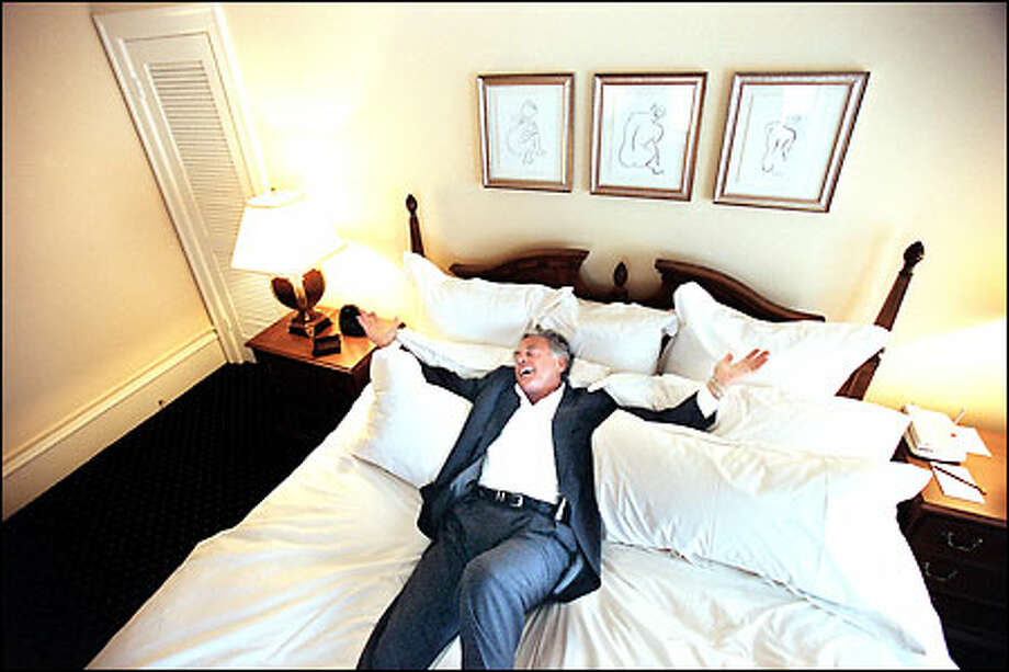 Michael Malone, owner of Seattle's historic Sorrento Hotel, flops onto a bed in one of the rooms to demonstrate the thought that went into putting it together. Photo: Paul Joseph Brown, Seattle Post-Intelligencer / Seattle Post-Intelligencer