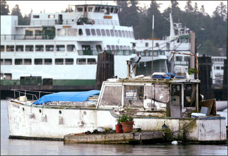 A live-aboard boat rests at anchor in Eagle Harbor off Bainbridge Island yesterday. The group Bainbridge Citizens United is suing the Department of Natural Resources, asking a court to order the state to force out such boats anchored in the harbor. A recent state law says such open-water marinas are the appropriate places for such live-aboards. Photo: Joshua Trujillo, Seattlepi.com / Seattle Post-Intelligencer
