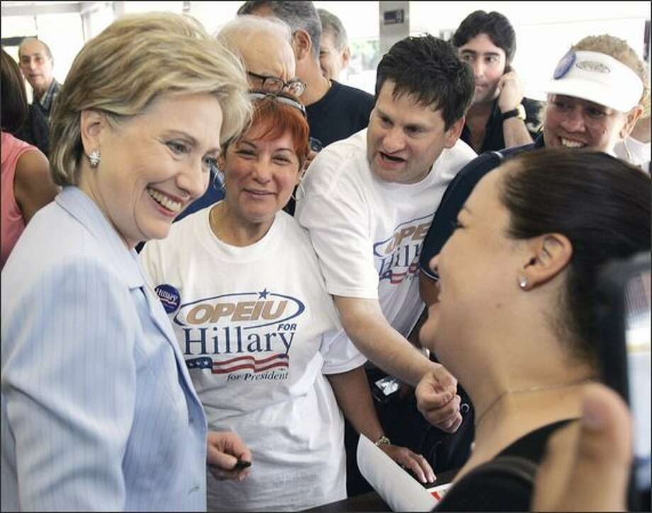 Democratic presidential hopeful Sen. Hillary Clinton chats with supporters at the Kasalta Bakery in San Juan, Puerto Rico, as she campaigns on primary day on Sunday. Photo: Associated Press / Associated Press