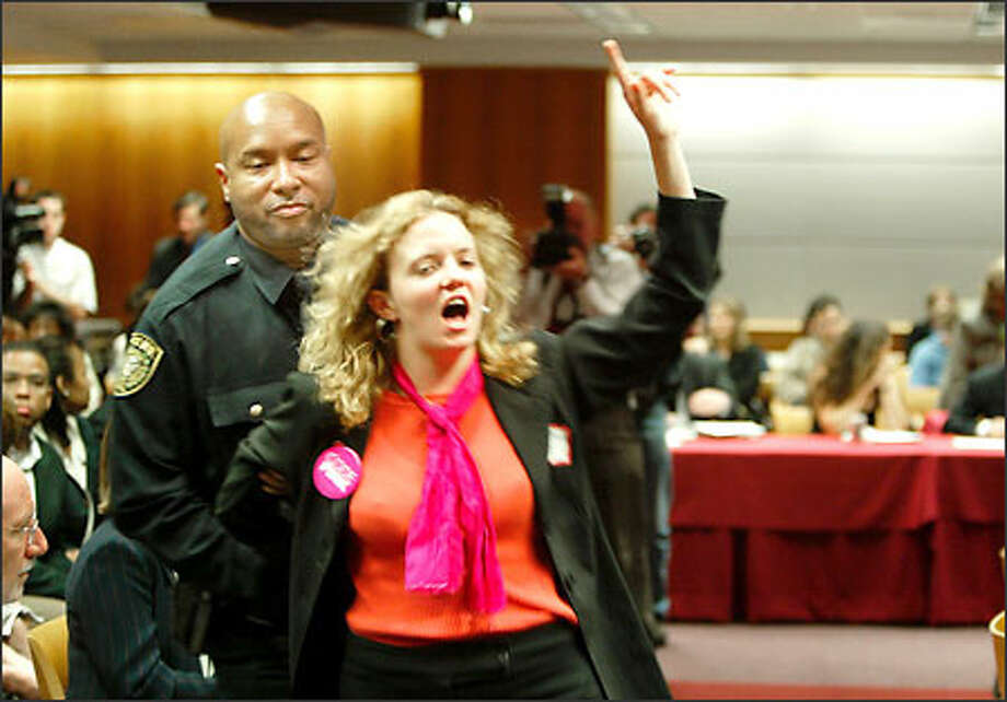 A woman is arrested yesterday while protesting during an FCC hearing on relaxing restrictions on media ownership in a single market. Photo: Associated Press / Associated Press