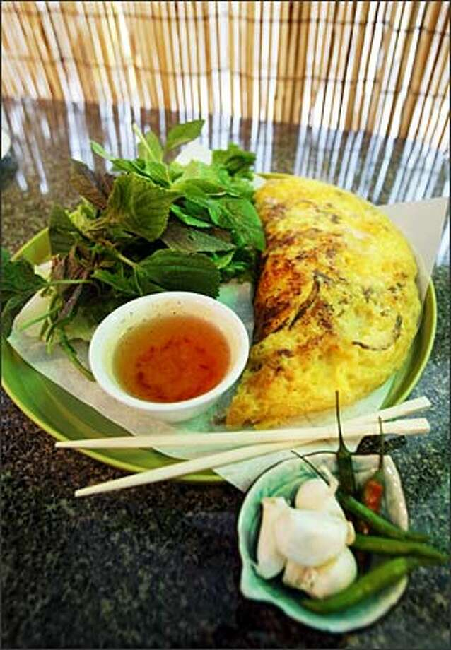 Lemongrass' banh xeo is beautifully presented. It's Vietnam's famous crackly yellow, folded rice-flour crepe filled with bean sprouts, shrimp and pork. Photo: Scott Eklund, Seattle Post-Intelligencer / Seattle Post-Intelligencer