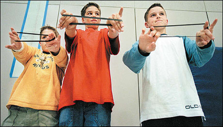 "Getting ""tech fit"": Elizabeth Blackwell Elementary sixth-graders, from left, Danny Kesl, Ryan Robertson and Cory Mehl, exercise their fingers with elastic bands in a unique weeklong program that teaches kids how to prevent repetitive-strain injuries from computer use. The Sammamish school's ergonomics program for elementary-age students may be the first in the nation. Photo: Paul Joseph Brown, Seattle Post-Intelligencer / Seattle Post-Intelligencer"