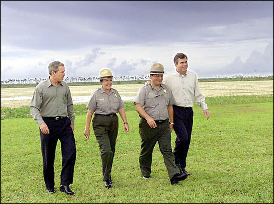 Political leaders love using national parks as photo backdrops.  They don't give park managers enough money.  Here, President George W. Bush,  left, and his brother, Florida Gov. Jeb Bush, right, tour the Everglades with Park Supervisor Maureen Finnerty and her deputy, Larry Belli. Photo: Associated Press / Associated Press