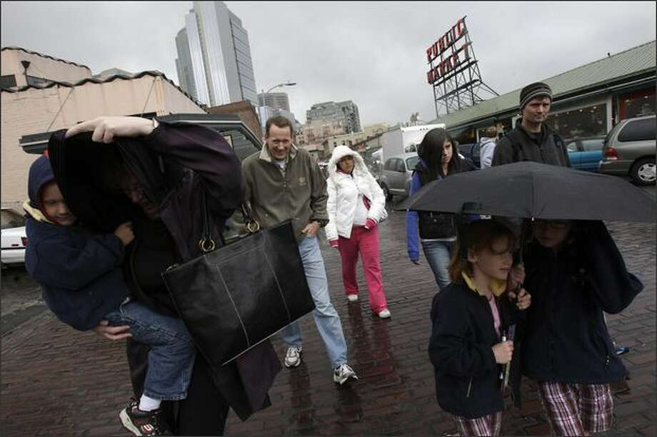 Trying her best to stay dry Friday, Cindy Bates, left, walks to the original Starbucks at Pike Place Market with her cousin Amy Stuart's family -- Stuart's son Ben, 5, in her arms, husband Jim, third left, and daughters, under umbrella, Jackie, 6, left, and Grace, 9. When Bates told Amy, unseen, to bring her family for a visit from Cincinnati, she baited them with the promise of 90-degree weather. They arrived Friday in summer clothes so bought discounted fleece tops from a gift shop, whose owner said he regrets lowering the prices when he thought summer was here to stay. Photo: Andy Rogers, Seattle Post-Intelligencer / Seattle Post-Intelligencer