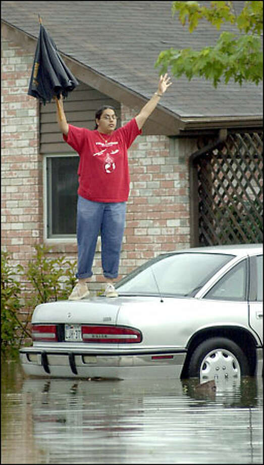 Veronica Espinoza stands on a car outside her home to alert rescue workers in south Houston that she and her family need help. Tropical Storm Allison, which was downgraded to a tropical depression after becoming the first named storm of the Atlantic hurricane season, dumped as much as a foot of rain in Texas and Louisiana Wednesday and yesterday. Remnants of the storm spread across the Deep South. Photo: Associated Press / Associated Press