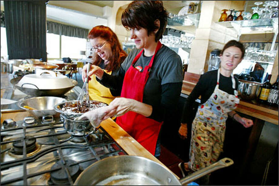 "D. Parvaz, center, heats ingredients for a Chocolate Decadence recipe in a class at the Blue Ribbon Culinary School with Traca Savadogo at her side. Parvaz calls herself ""the ultimate culinary reprobate,"" but she survived the six-week program and learned to cook a little. Photo: Paul Joseph Brown, Seattle Post-Intelligencer / Seattle Post-Intelligencer"