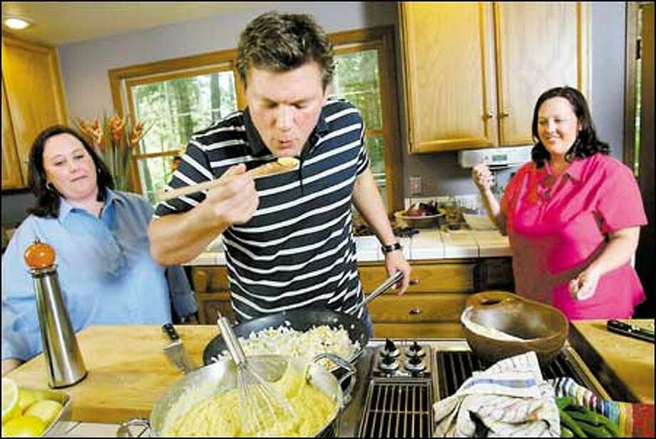 "Tyler Florence takes a taste between taping sessions last Thursday of ""Food 911."" Florence was in Sammamish to rescue Wendi Oglesby, right; her twin, Cindi, lent moral support. Photo: Dan DeLong, Seattle Post-Intelligencer / Seattle Post-Intelligencer"