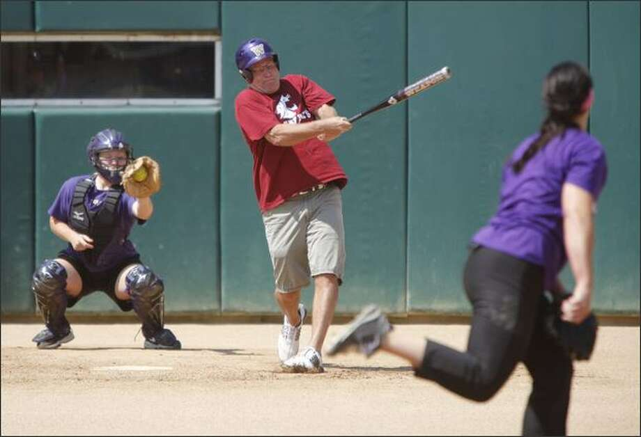 Coug and seattlepi.com columnist Jim Moore swings at a pitch thrown by UW softball star Danielle Lawrie at Husky Softball Stadium on Monday afternoon. Photo: Clifford DesPeaux, Seattlepi.com / seattlepi.com