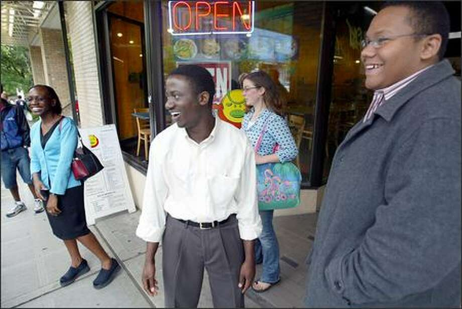 UW senior Eric Mvukiyehe, center, meets friends for lunch at Honey Bee's. Mvukiyehe earned a full-ride scholarship for graduate school at Columbia University in New York. Photo: Paul Joseph Brown, Seattle Post-Intelligencer / Seattle Post-Intelligencer