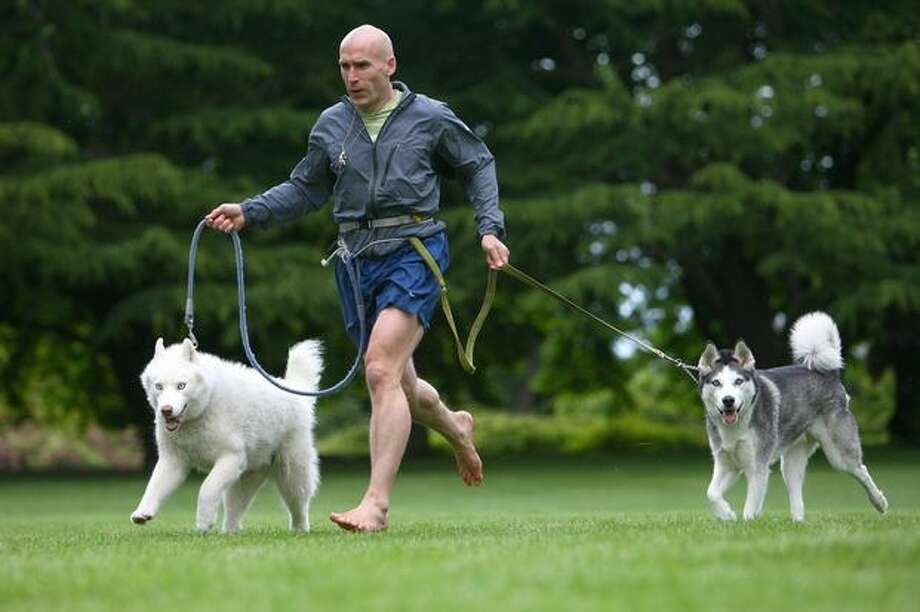 """Barefoot"" Ted McDonald runs with his dogs Hiko, left, and Eddie on June 9 at Volunteer Park in Seattle. Photo: Joshua Trujillo, Seattlepi.com / seattlepi.com"