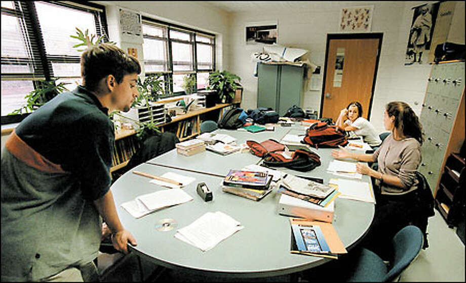 Eleventh-grader Jason Watts; Amy Bayer a school adviser (teacher); and Jennifer Camara (in the background) also in the 11th-grade, during a class at the innovative Met school in Providence. Photo: Phil H. Webber, Seattle Post-Intelligencer / Seattle Post-Intelligencer