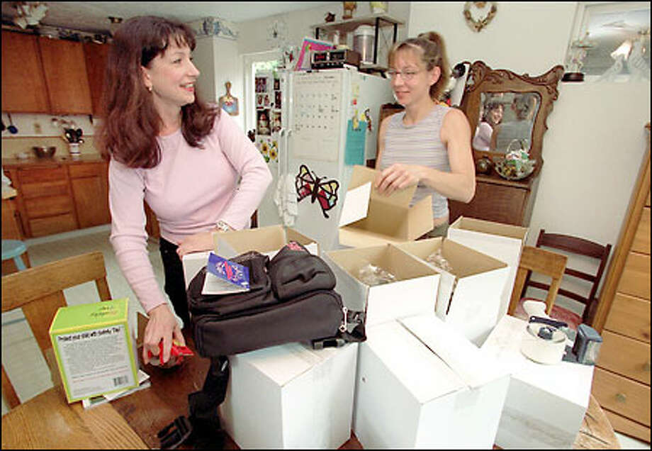 Shawn Boice, founder of In Touch, and her sister, Tammy Janes, package Daddy Gear bags in Boice's home in Bothell for shipment for Father's Day. Photo: Phil H. Webber, Seattle Post-Intelligencer / Seattle Post-Intelligencer