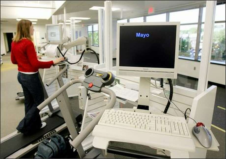 "A woman works out while she works on Dr. James Levine's brainchild, a workstation that combines a computer, desk and treadmill. The ""ultimate office makeover"" offers an alternative to being sedentary in front of a computer, according to the Mayo Clinic obesity doctor, who also uses a treadmill on the job. Photo: Associated Press / Associated Press"