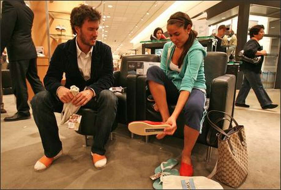 Blake Mycoskie, founder of Shoes for Tomorrow, or TOMS, talks with Hannah Dougherty of Seattle as she tries on a pair of TOMS at the downtown Nordstrom. Photo: Mike Urban, Seattle Post-Intelligencer / Seattle Post-Intelligencer