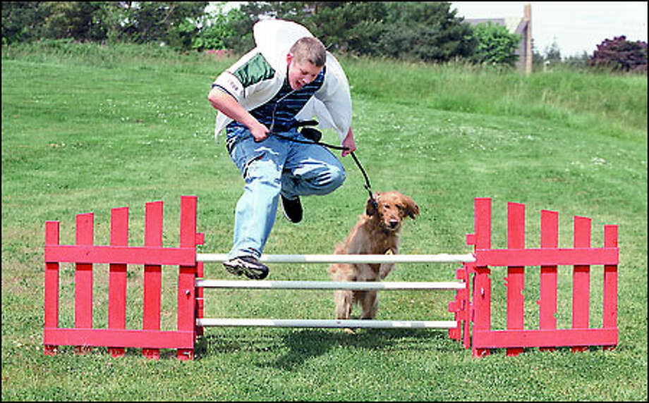 Overcoming hurdles: Oak Harbor Middle School student Michael Barrett, 14, and his charge, Morgan, a 2-year-old golden retriever, breeze through an agility course. Photo: Gilbert W. Arias, Seattle Post-Intelligencer / Seattle Post-Intelligencer