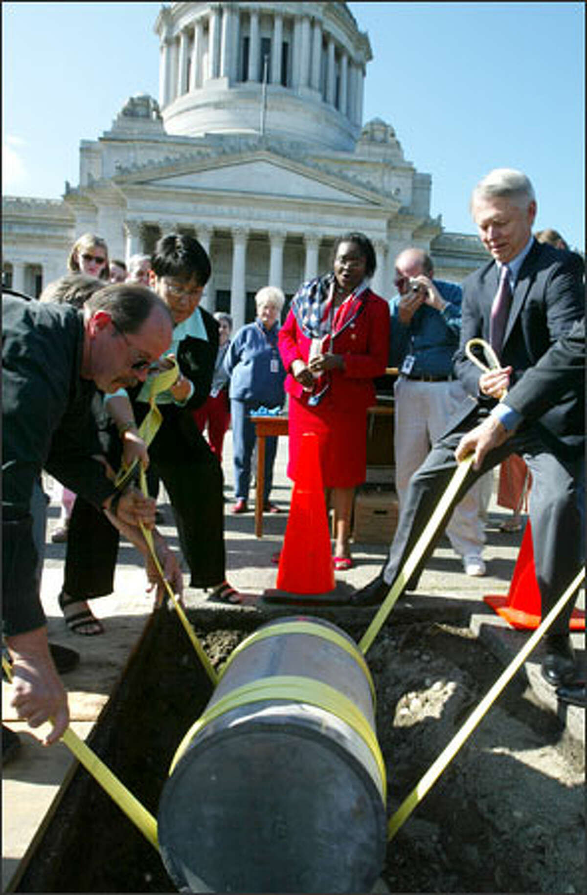ecretary of State Sam Reed, right, joins other officials to lower a 1953 time capsule into the ground outside the state Capitol on Thursday. The capsule had been missing for nearly half a century until it was found in 2002.