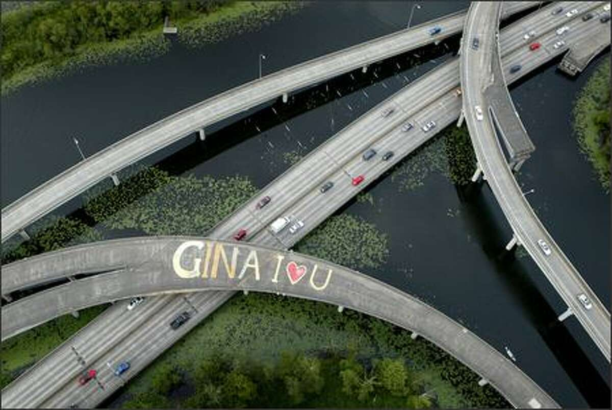 """A message of love to an unknown """"Gina"""" is scrawled across the lanes of an overpass on Highway 520 in the Arboretum on Tuesday in Seattle. The message was painted on an unused ramp on the highway in the serene park. The painter and the recipient of the message are mysteries."""