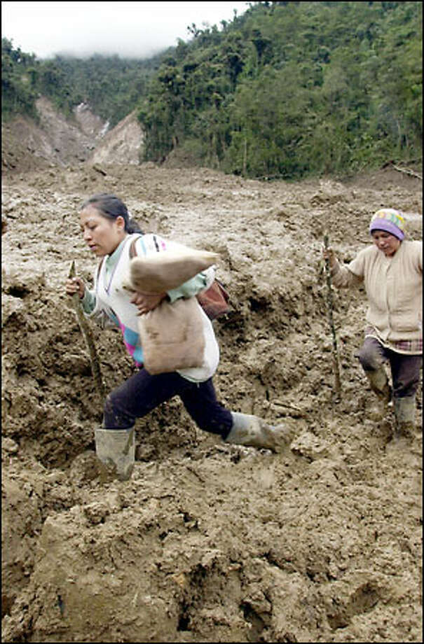 Two women wade through a mudslide in Quebrada Negra, a rural area about 30 miles east of Quito, Ecuador, yesterday after days of torrential rains. Rescue workers struggled to recover the bodies of at least 31 people buried by a landslide Tuesday as they took refuge in a home in the Andes near Papallacta. Among the victims was the homeowner, who had invited about 30 people in when their bus became blocked by other landslides. A civil defense official said at least 48 people have been killed by landslides or drowned in Ecuador's Andes and Amazon jungle after four days of heavy rain. Photo: Associated Press / Associated Press
