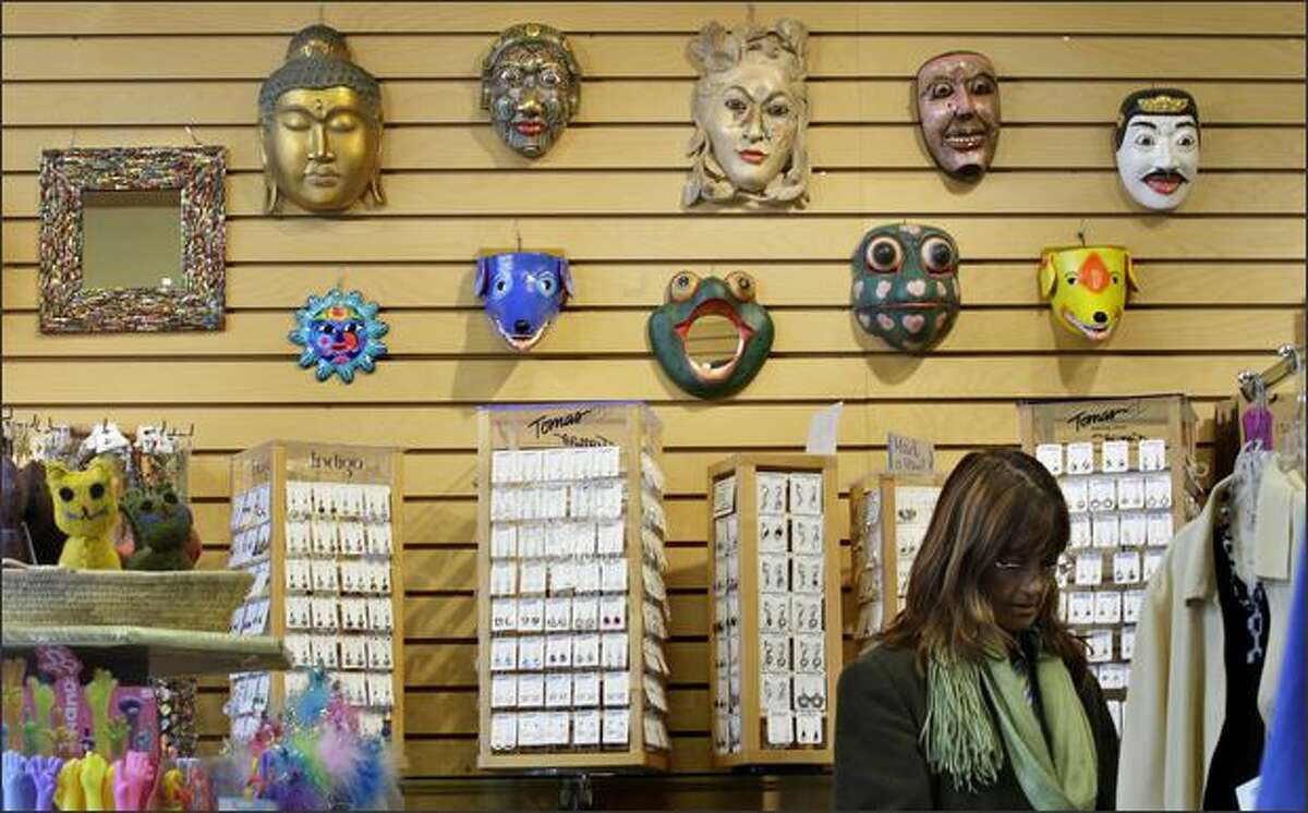 Zamboanga regular Teresa Rogers of Beacon Hill checks the clothing at the West Seattle store under the watchful eyes of Balinese and Mexican masks.