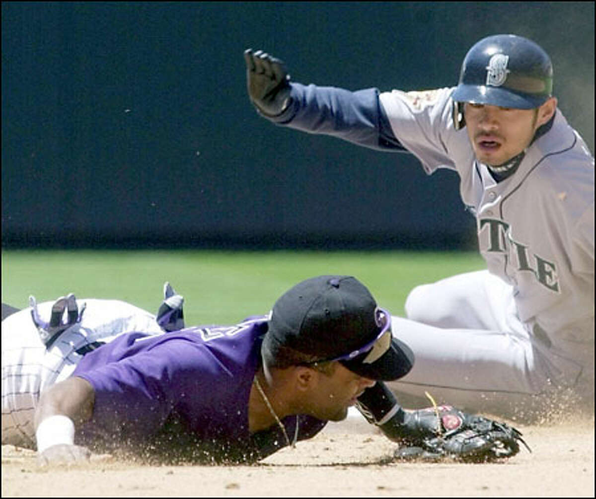 Rockies shortstop Neifi Perez falls in front of second base after missing the throw as Ichiro Suzuki steals second in the first game yesterday.