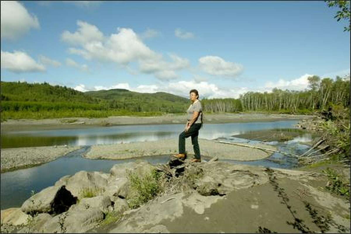 Mary Leitka, Hoh chairwoman, looks over the Hoh River from a pile of flood debris. The river has changed course over the years, and officials say the reservation may be doomed.