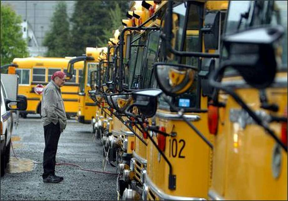 Peter Zagorski, with Wingfoot Commercial Tire, watches as Renton school buses get their tires refilled Friday morning.  Pranksters let the air out of the front tires on every one of the Renton district's school buses, delaying classes by two hours districtwide and closing Renton High School on the last day of school in the district. Photo: Karen Ducey, Seattle Post-Intelligencer / Seattle Post-Intelligencer
