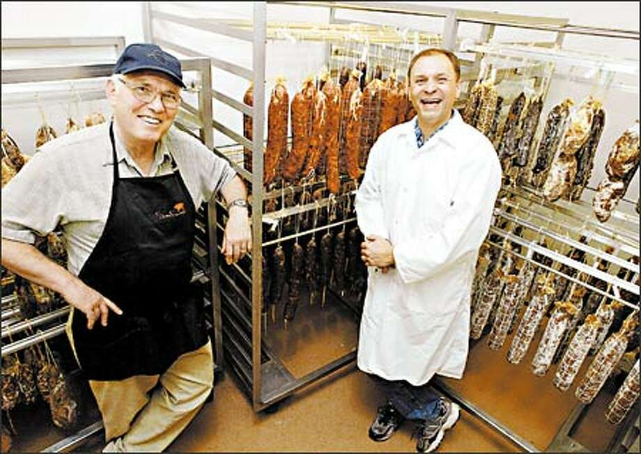 Armandino Batali, left, and his son-in-law, Brian D'Amato, in the expanded curing room that will allow Salumi to make more meats to sell wholesale to restaurants and delis. Photo: Meryl Schenker, Seattle Post-Intelligencer / Seattle Post-Intelligencer