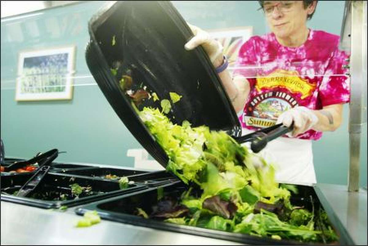 Tracy Doerschel refills the mixed salad greens at the Bastyr University cafeteria.