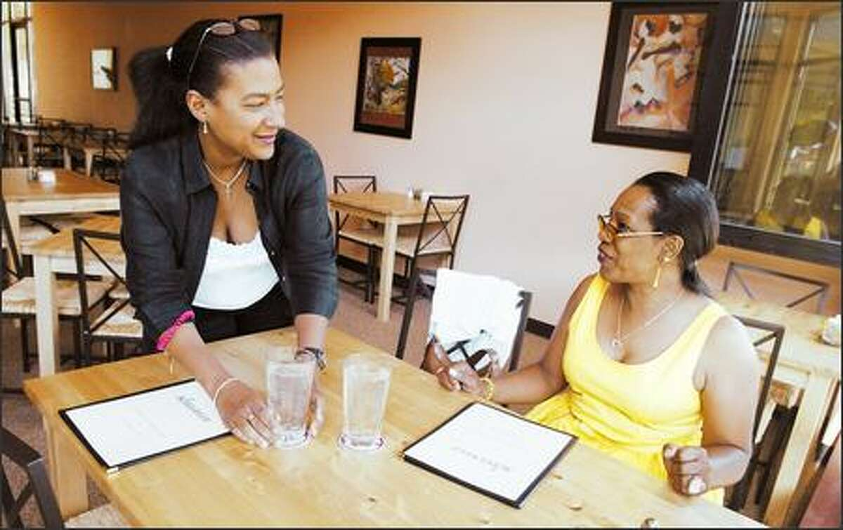 Gail Williams, left, co-owner of Kallaloo, greets customer Ava Carey. The Columbia City restaurant has been open since March.