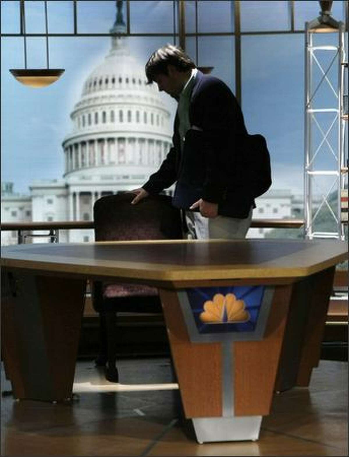 Luke Russert, son of Tim Russert, touches the empty chair that was his father's on the set of