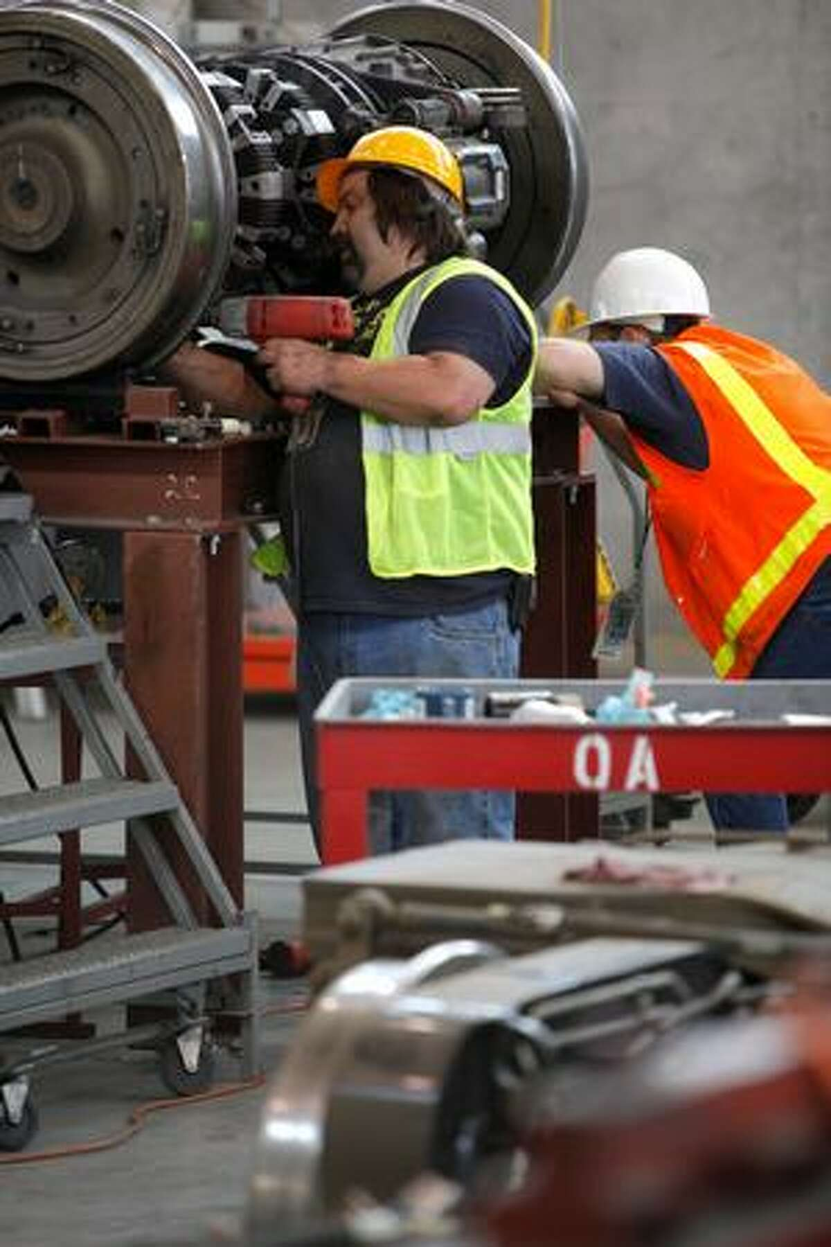 Employees work on a wheel assembly at the Light Rail Link Operations and Maintenance Facility in Seattle.