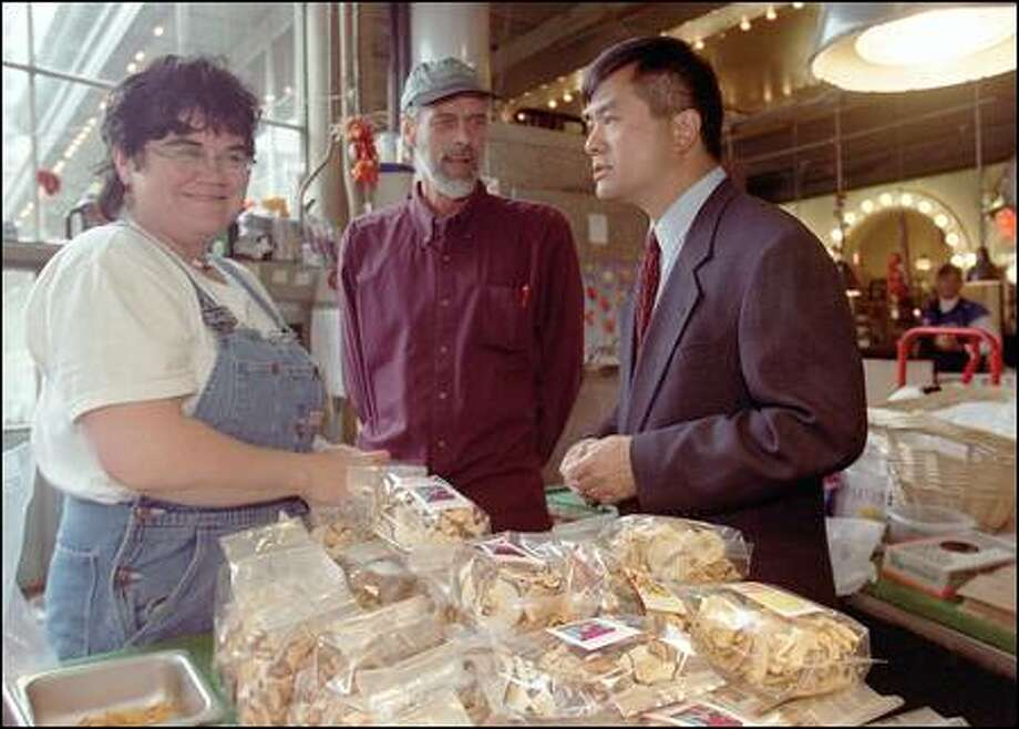Gov. Gary Locke, right, chats with Denice Gubernick and Paul Sweat at the Simple and Sweet Organic Produce stall at the Pike Place Market. Photo: Phil H. Webber, Seattle Post-Intelligencer / Seattle Post-Intelligencer