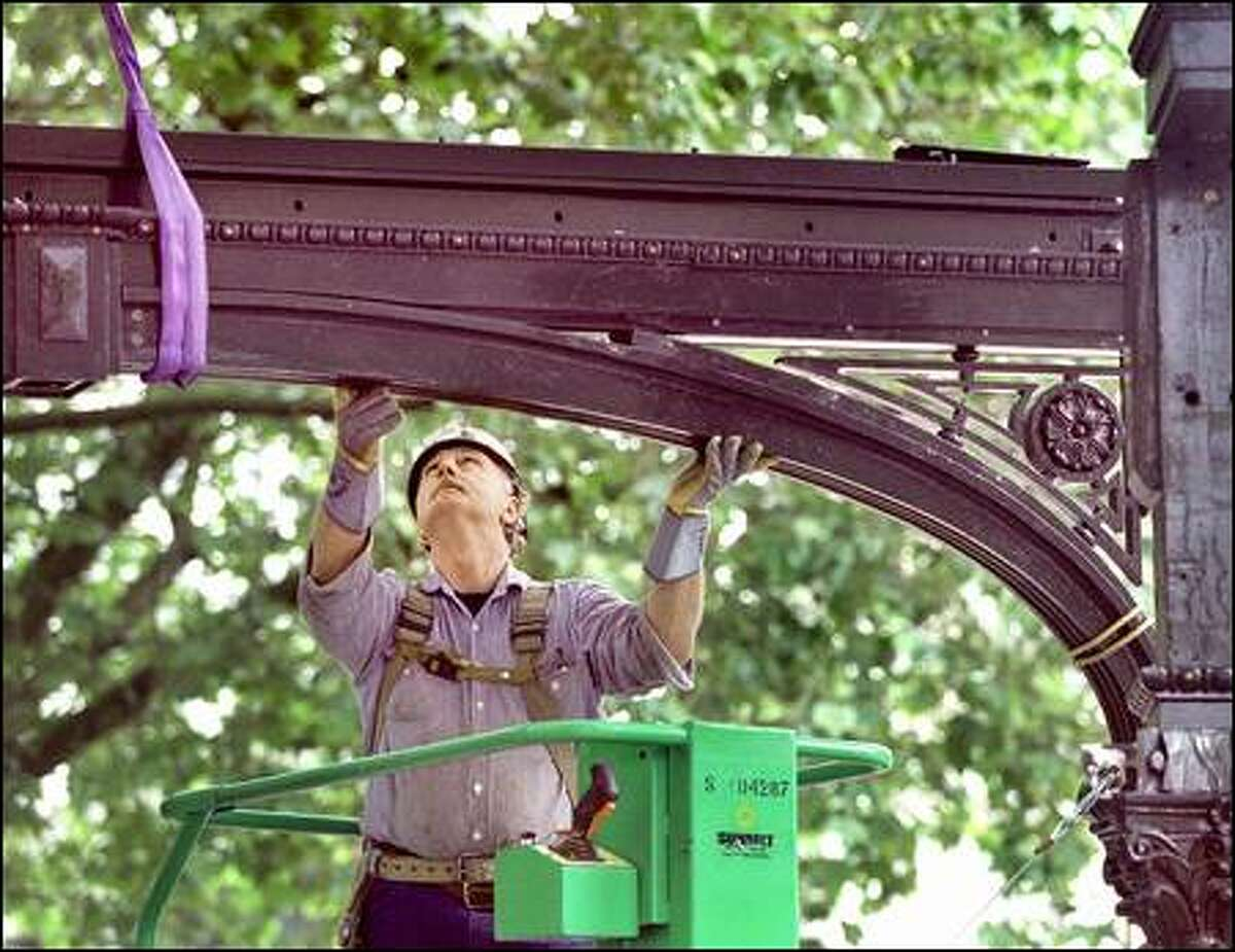 Larry Bluhn concentrates on placing the first piece of iron arch on top of two beams on the restored pergola in Pioneer Square. He delayed retirement to work on it.