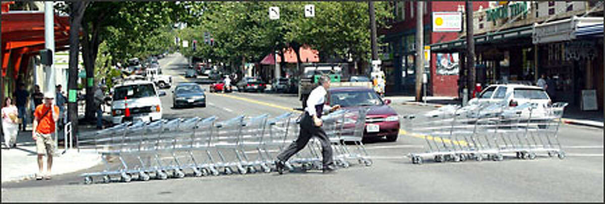 Raymond Glandon, store director at the Fremont PCC Natural Market, moves shopping carts to the new PCC, which opens today at 600 N. 34th St., about 500 feet west of the old PCC. The new store is about twice the size of the old one.