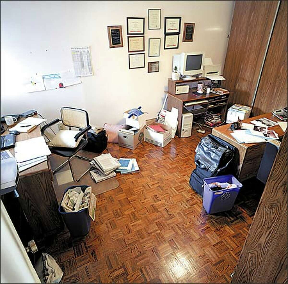 This dull, dim, cluttered workspace was a wasteland of castoff furniture, low lighting and boxes of papers.