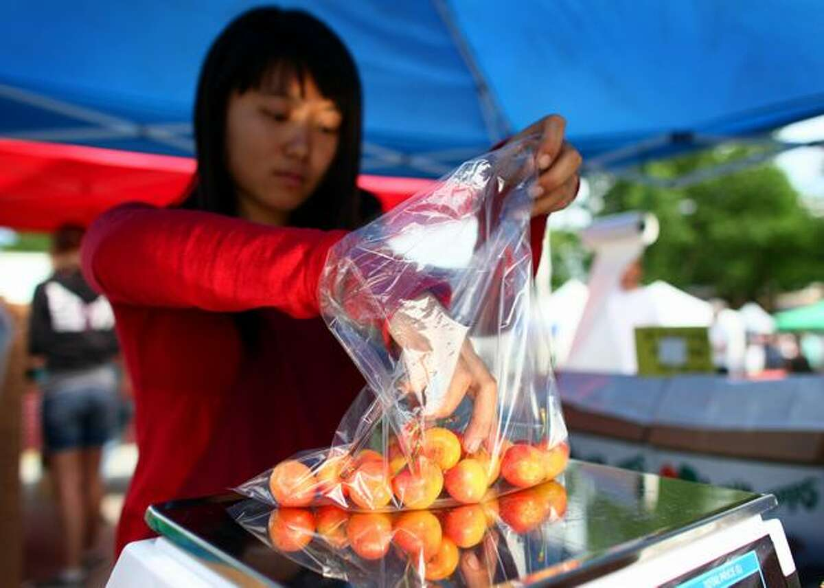 Julia Yao with Lyall Farms of Mattawa, Wash. weighs a bag of Rainier cherries at the Lake City Farmers Market on Thursday. The cherries, a favorite fruit of the Pacific Northwest, have made an early appearance this year.
