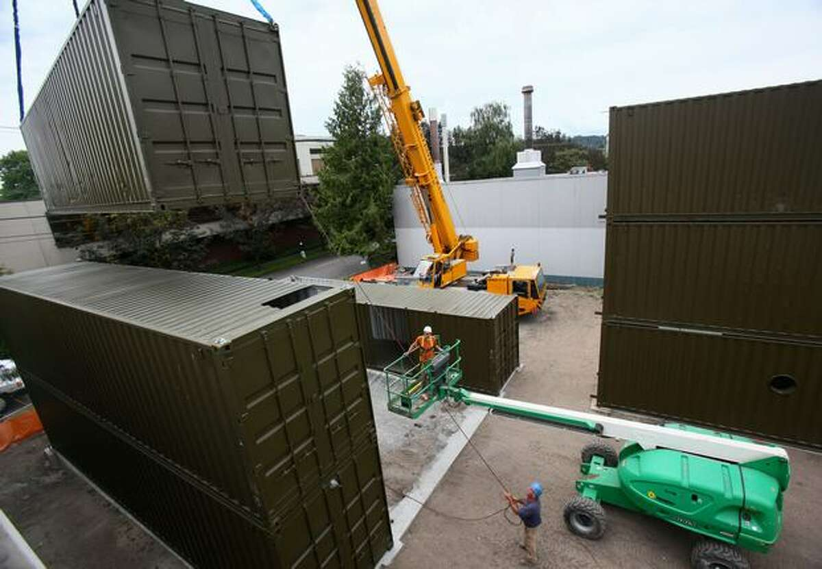 Workers from Fogarty Construction stack shipping containers as they construct a building out of the containers in Seattle's Georgetown neighborhood on Thursday, June 18, 2009.