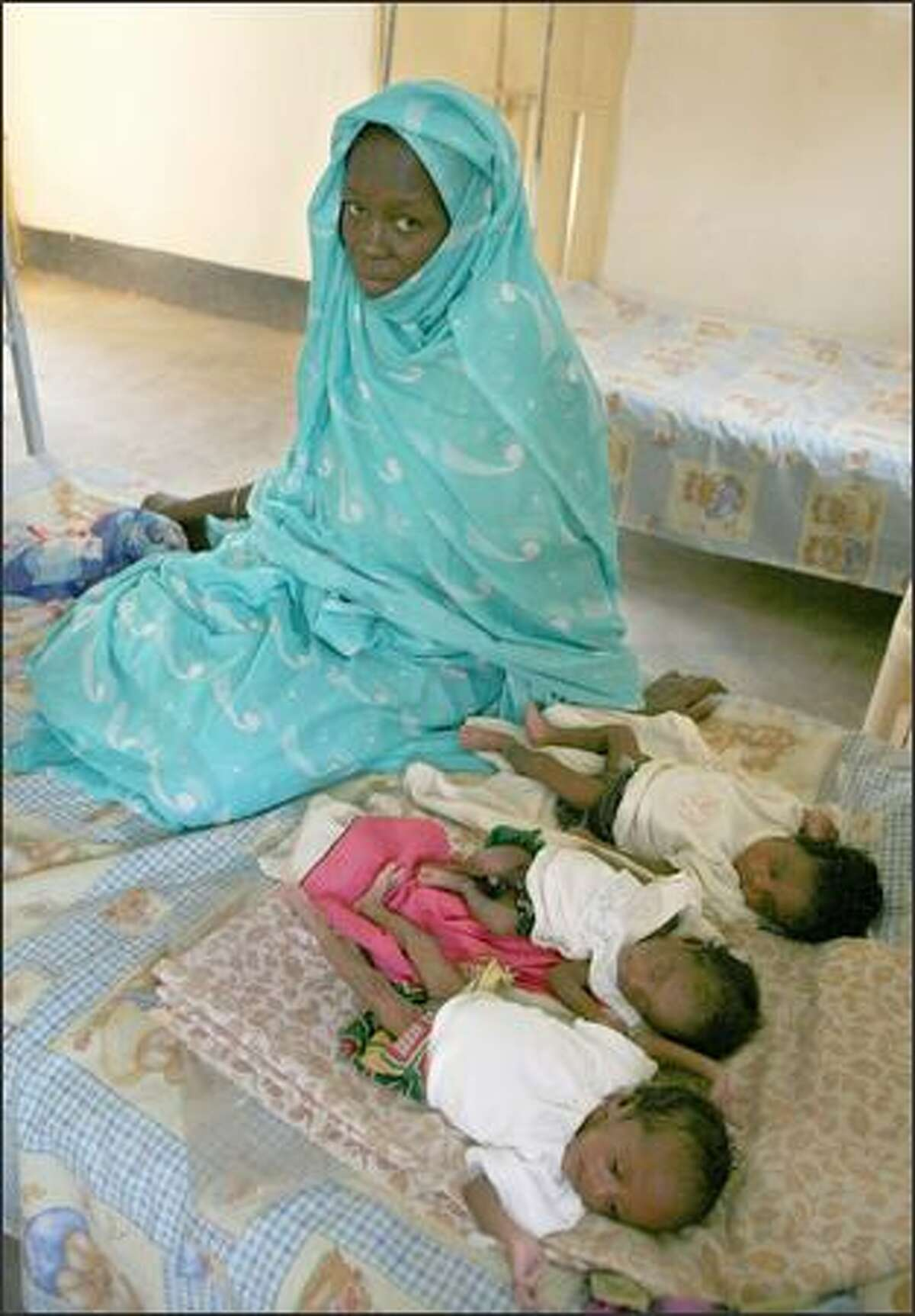 Myriam Ibrahim, a 28-year-old mother of 1-month-old triplets, sits next to the girls at El Fasher Therapeutic Feeding Center in the Darfur town of El Fasher, Sudan, last Thursday.