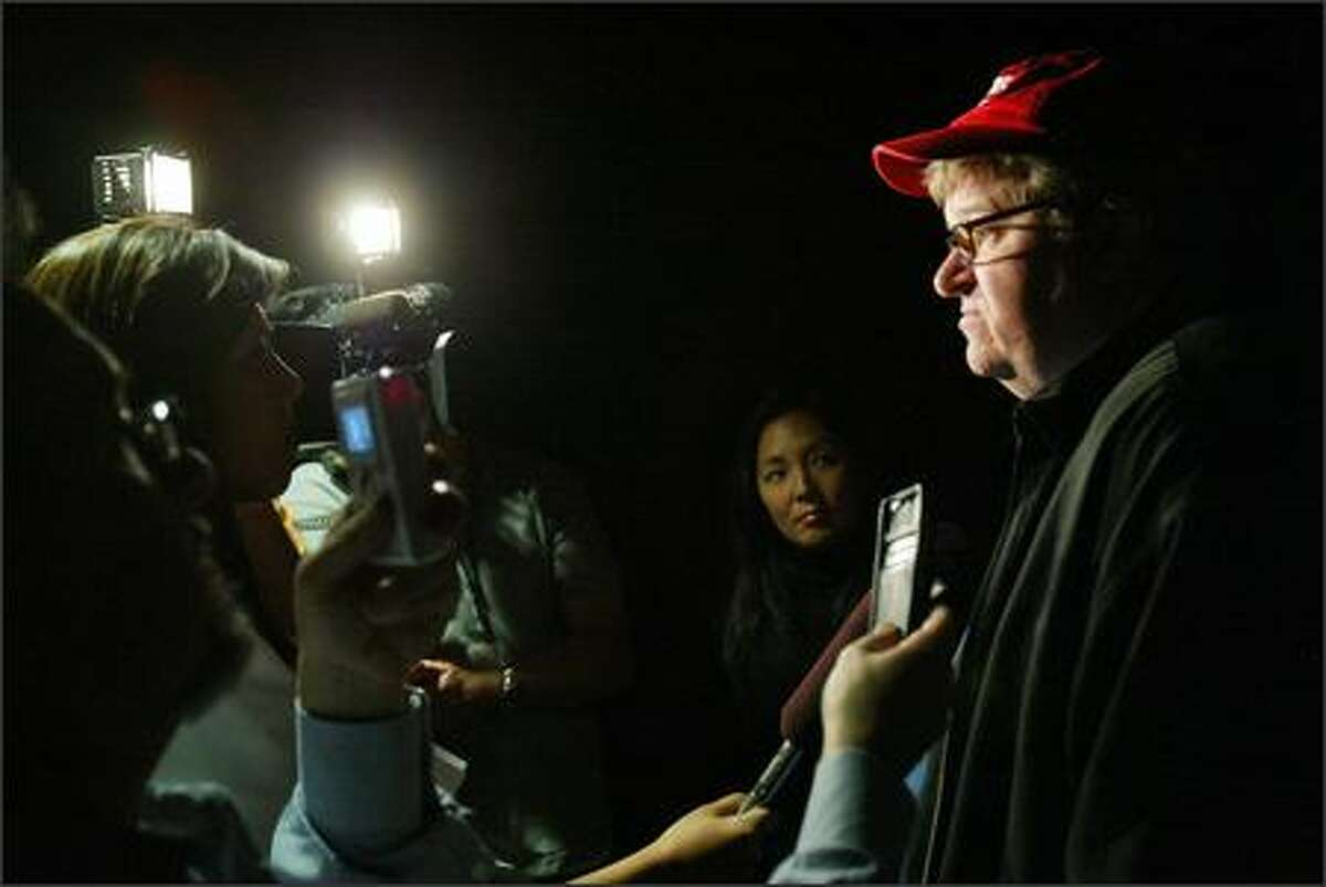 Director Michael Moore talks with the media before a screening of his film