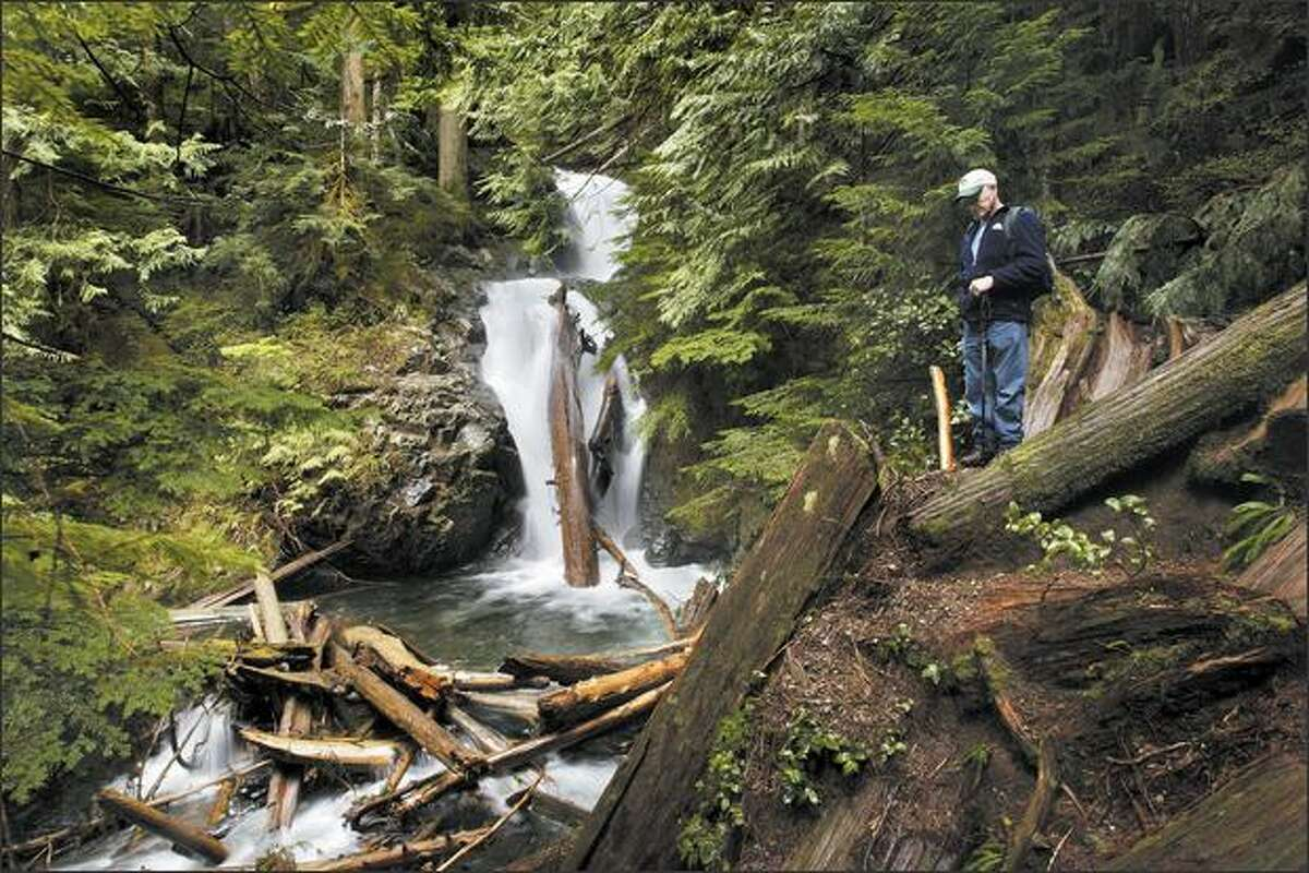 Waterfaller Bob Mooers stops to appreciate Confusion Falls while hiking along Twentytwo Creek as it exits Lake 22 near Granite Falls.