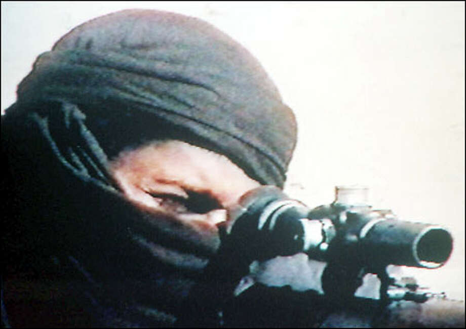 An image from television shows an unidentified masked man with a rifle in an undated recruitment tape promoting Osama bin Laden's organization. Photo: Associated Press / Associated Press