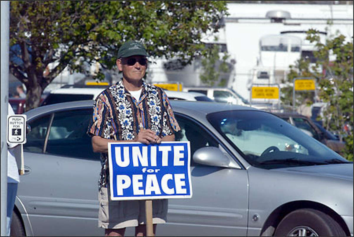 """Protests at the intersection of Commercial and 12th avenues in Anacortes. """"I'm staying here until peace breaks out,"""" says Howard Pellett."""