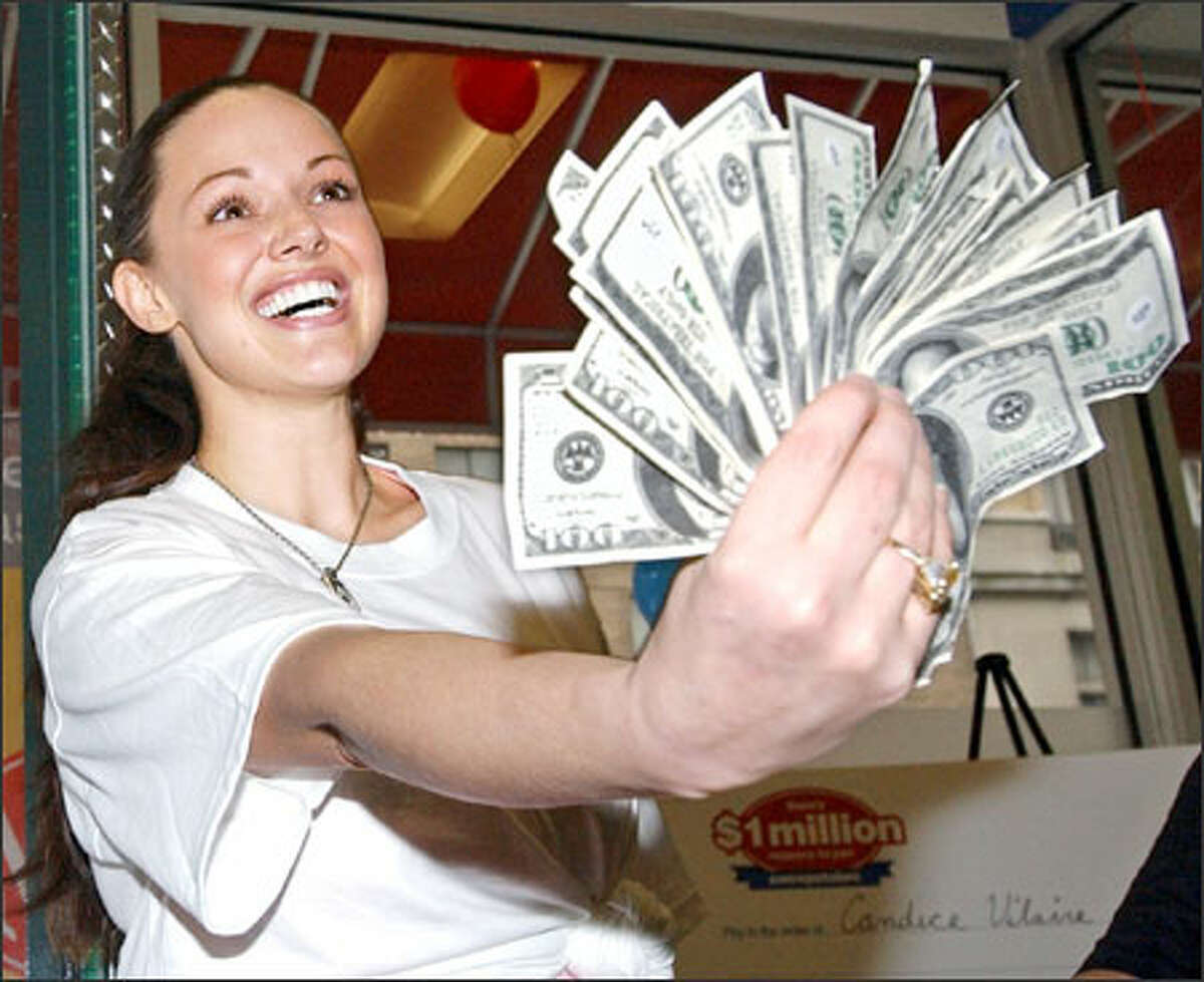 Anna Benson, wife of New York Mets pitcher Kris Benson, holds up a fistful of cash during a cash giveaway at a sports bar in New York.