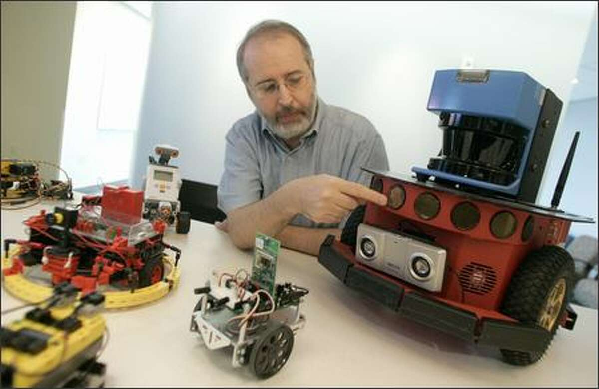 Microsoft's Tandy Trower points out various functions of the Mobile Robot Pioneer P3, right, along with other robots from outside companies for which Microsoft is developing universal robotic software.