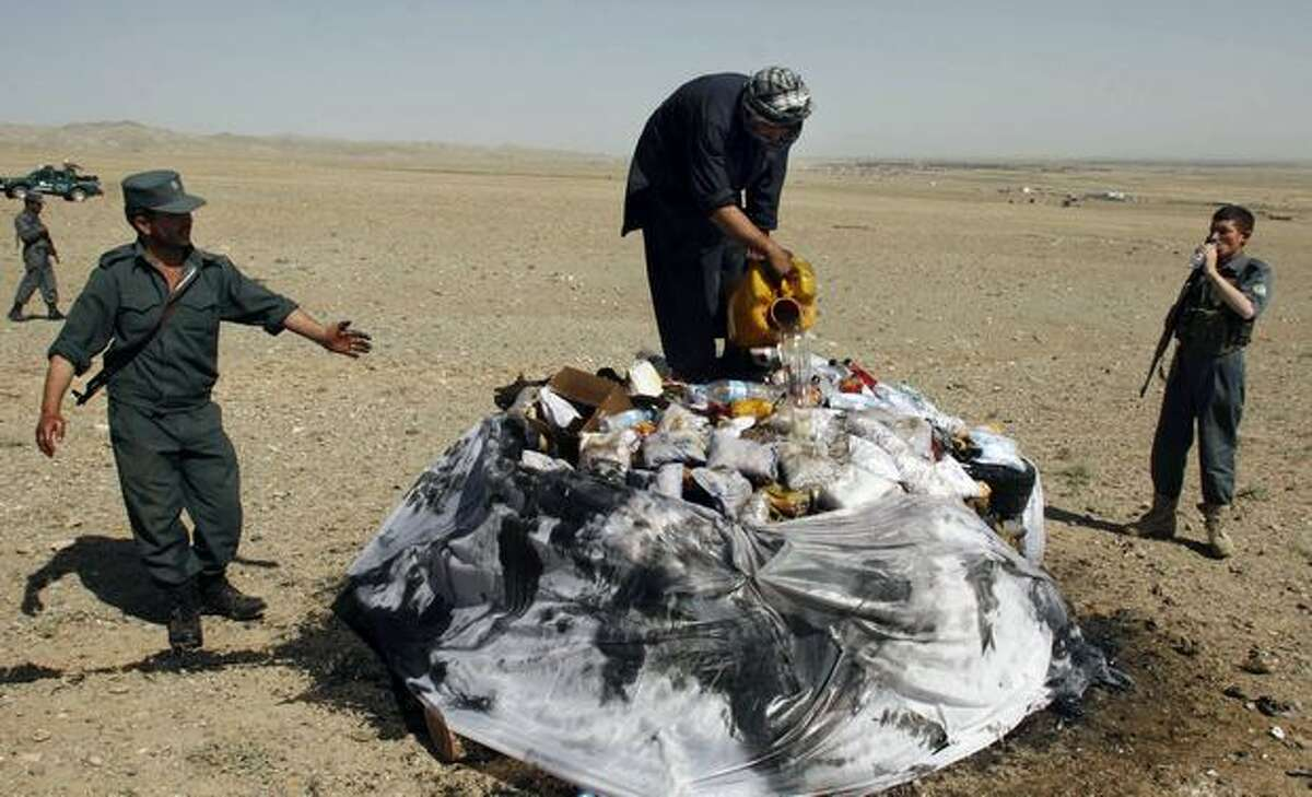 An Afghan man pours fuel during a drug burning ceremony in Herat city west of Kabul. (AP Photo/Fraidoon Pooyaa)