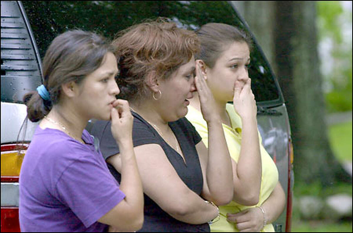 Rosaura Godoy, left, and two other women watch police investigate the apparent drownings of five children at a home in their Houston neighborhood yesterday.