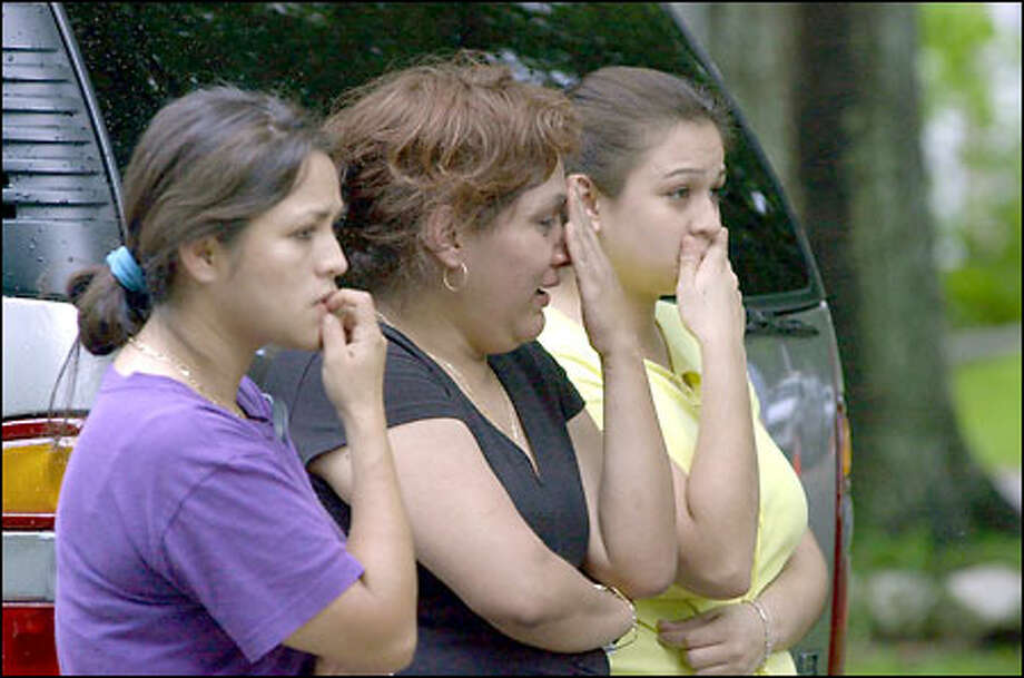 Rosaura Godoy, left, and two other women watch police investigate the apparent drownings of five children at a home in their Houston neighborhood yesterday. Photo: Associated Press / Associated Press