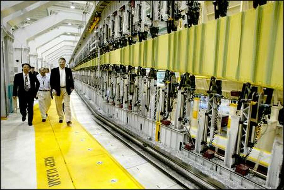 Lars Andersen, right, program manager of the longer-range 777 models, walks alongside a 299-foot-long automated assembly tool.